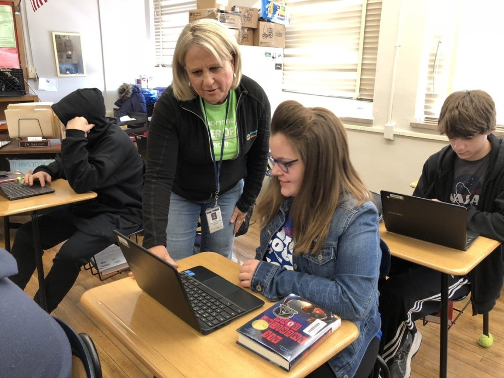 Teacher and student working on a laptop